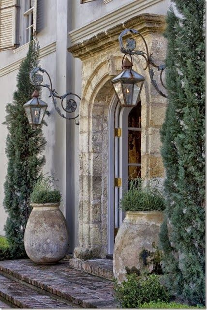 Magnificent entry to a French Country home or French farmhouse. Large antique French pots and cypress trees flank the arched doorway. #frenchfarmhouse #frenchchateau #frenchcountry #curbappeal #chateaudomingue #houseexterior #oldworld