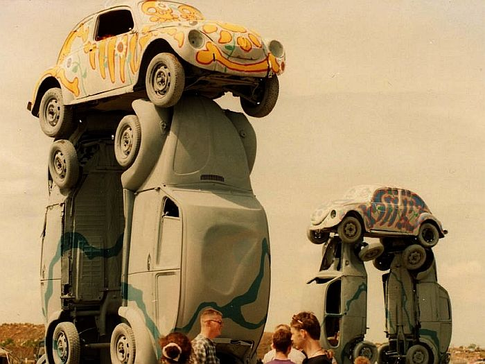 """Dubhenge: """"In 1996, a group of artists who call themselves Hugh Jart (get it?) set up this henge for the Beetle Bash at Avon Park Raceway for summer solstice. It was a Stonehenge replica made of donated junk VWs, both VW beetles and buses or kombis."""" —Clonehenge, a blog."""