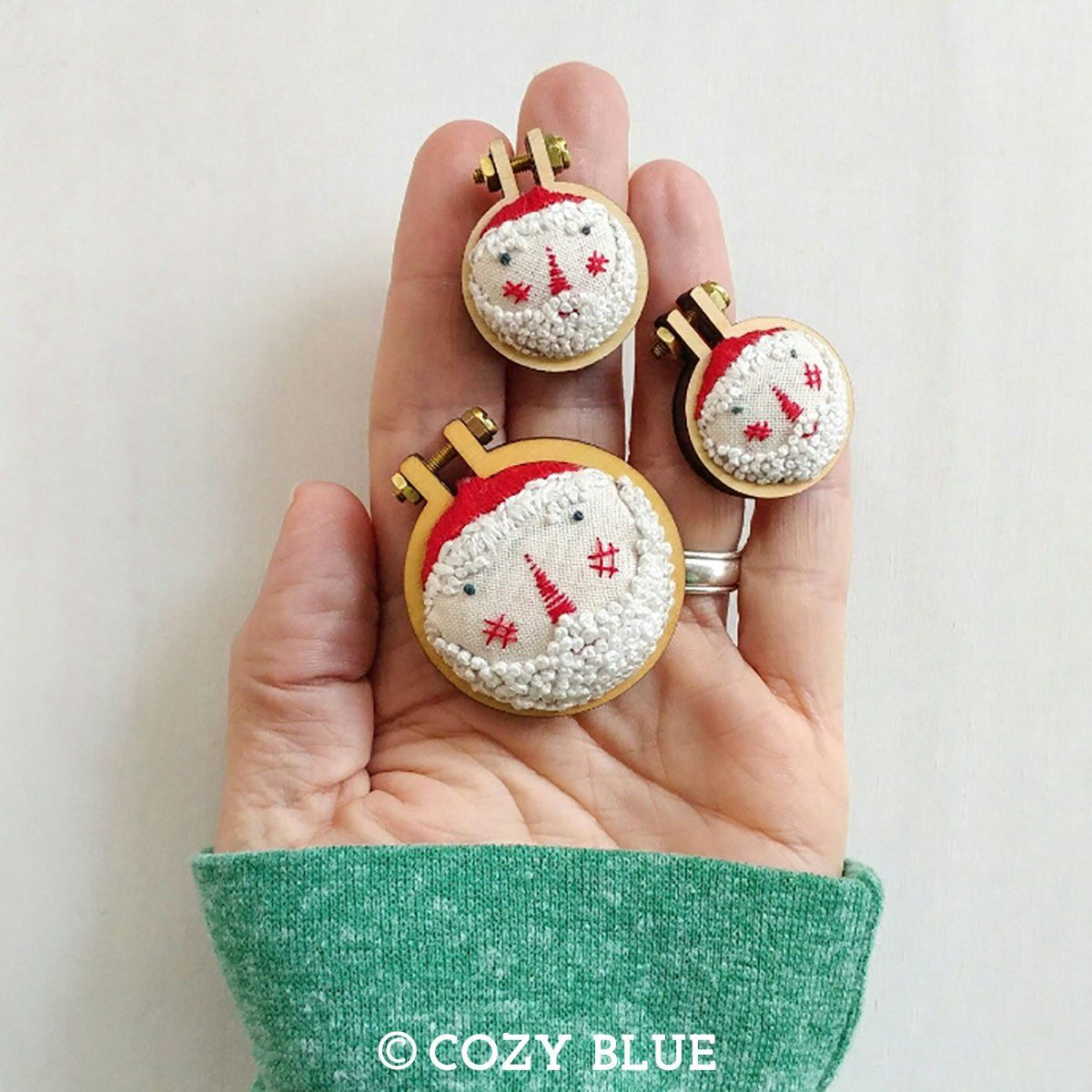 """Class meets: 12/06/17, 6pm - 8pm Stitch an adorable mini Santa to hang on your tree for the holidays! The wee pattern is designed by Liz of Cozyblue Handmade and uses Dandelyne's mini embroidery hoops. Requires a 4-6"""" embroidery hoop for stitching, Dandelyne mini hoop for framing (size 1"""", 1.6"""", or 2.2""""), 1 fat quarter or 1/4 yd of solid fabric, embroidery needles, assorted embroidery floss colors (sample uses red, white, and black) - get 15% off at Fancy Tiger Crafts."""
