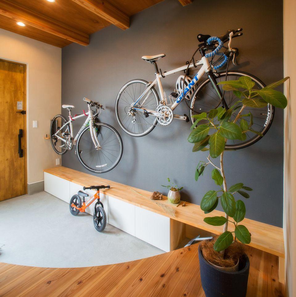 広く取った玄関スペースの壁に 趣味のロードバイクを掛けてカッコよく収納 省スペースかつ実用的なので ときどき提案してます 事前に壁を補強しておけば後付けもできます 自転車の下には造作で 腰掛けにもなる靴箱を作りました 上がり框を曲線にする