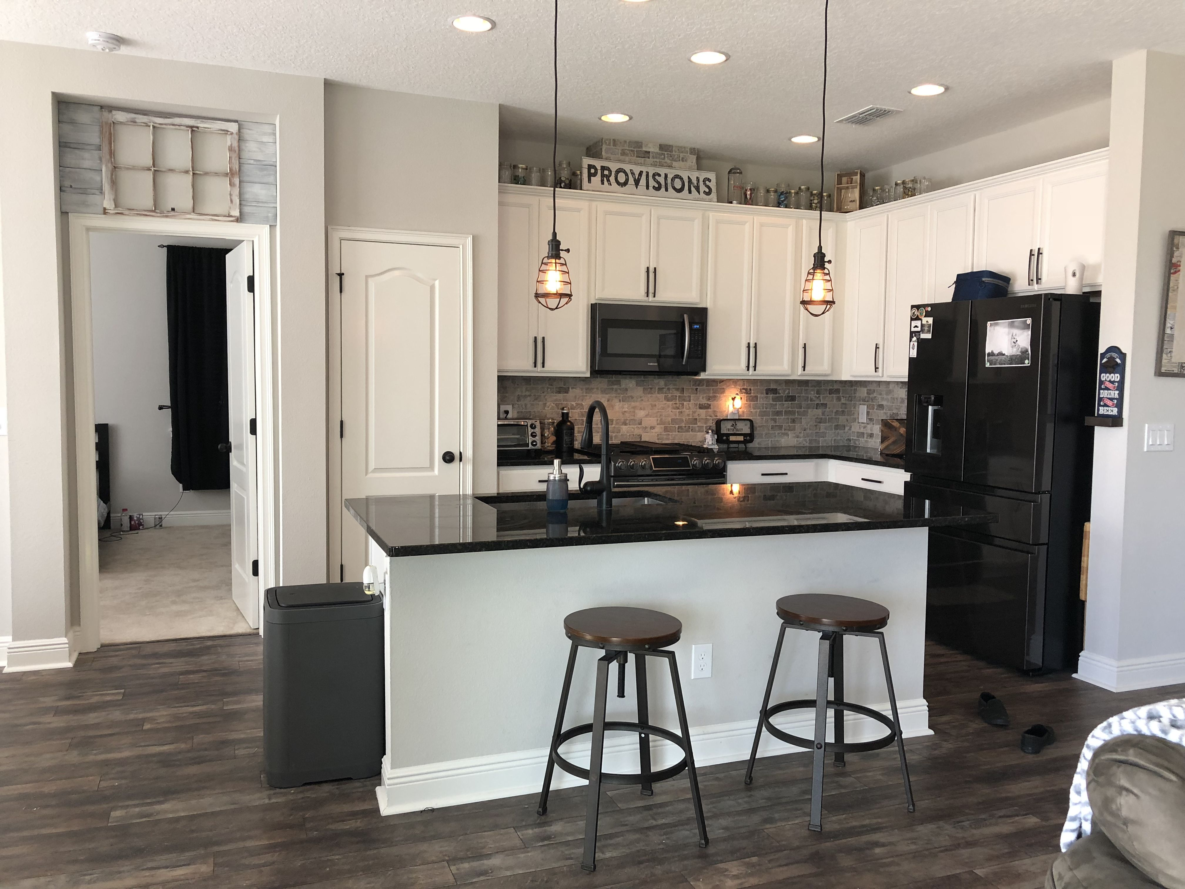 Industrial Style Farmhouse Kitchen With Black Granite Counter Tops And White Cabinet Black Appliances Kitchen White Cabinets Black Appliances Black Countertops