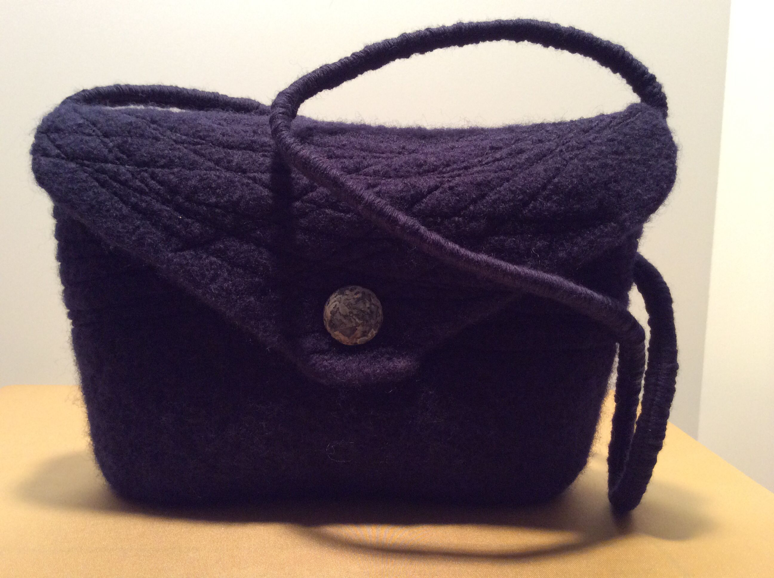 Hand knit and fulled bag by Elaine Haag, 2014.  This handbag features a brocade lining, interior pocket, freestyle stitching, magnetic closure and a denim lapis stone.