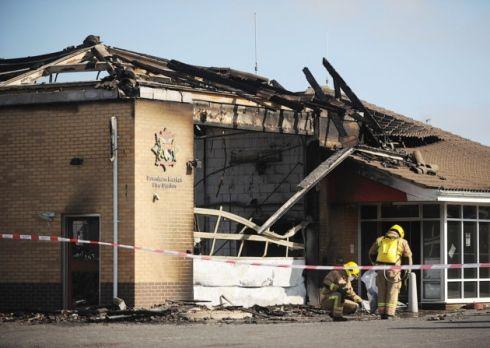 Het brandt niet enkel bij de buren... Firefighters surveying the devastation after the fire at Downham Market fire station. Picture: Ian Burt