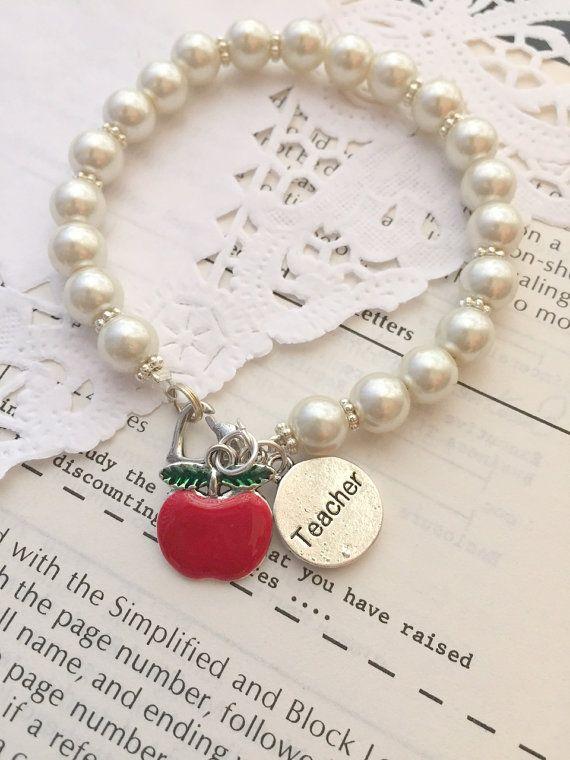 Teacher, apple charm, glass pearl bracelet.  ***************************************************  It is the supreme art of the teacher to awaken joy