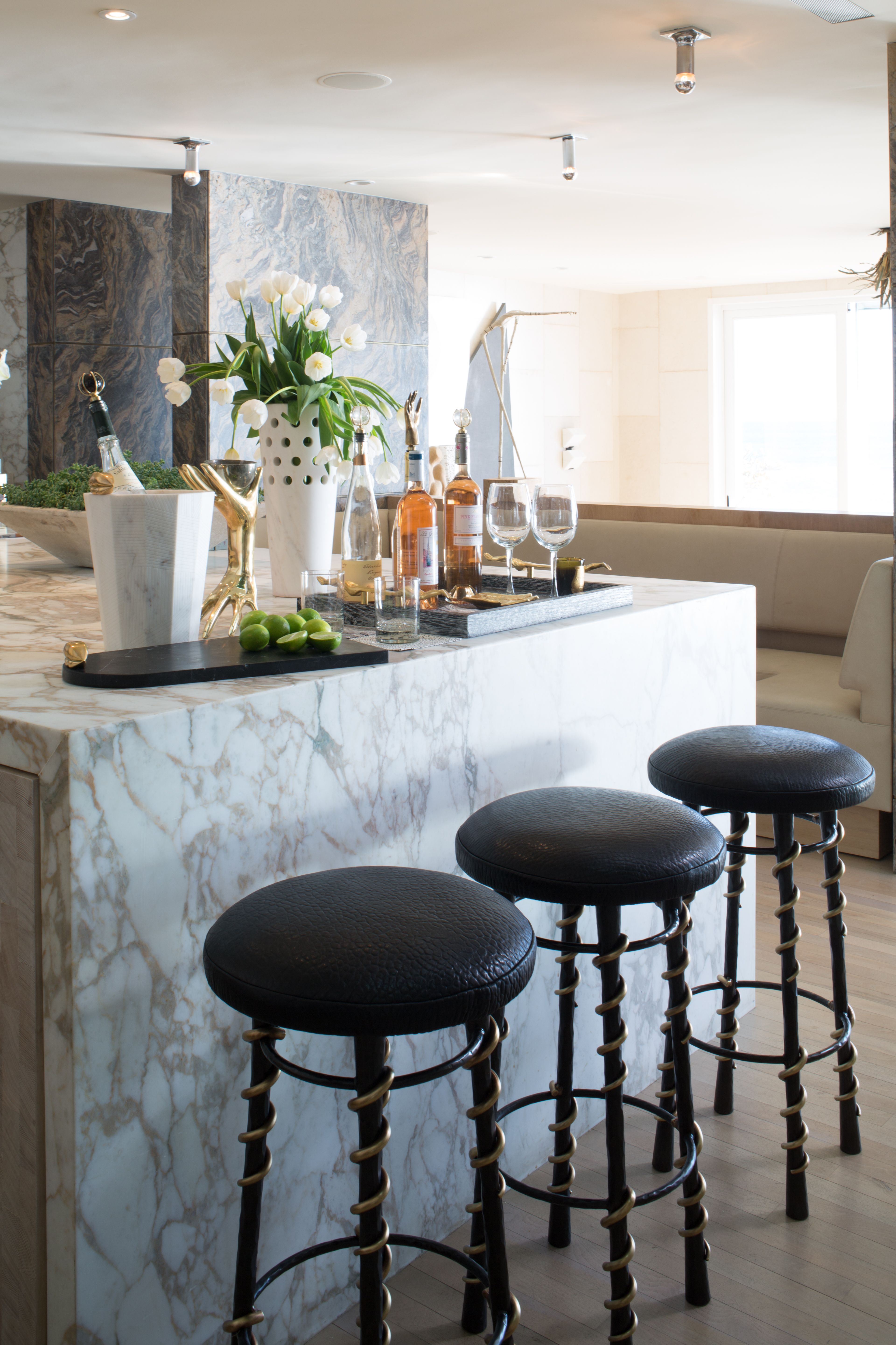 KELLY WEARSTLER   SERPENT BAR STOOL. Hand-wrought blackened steel legs with bronze serpent-inspired detailing and supple black textured leather upholstery