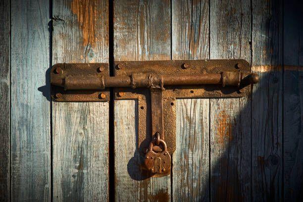 metal latch with padlock on the wooden door