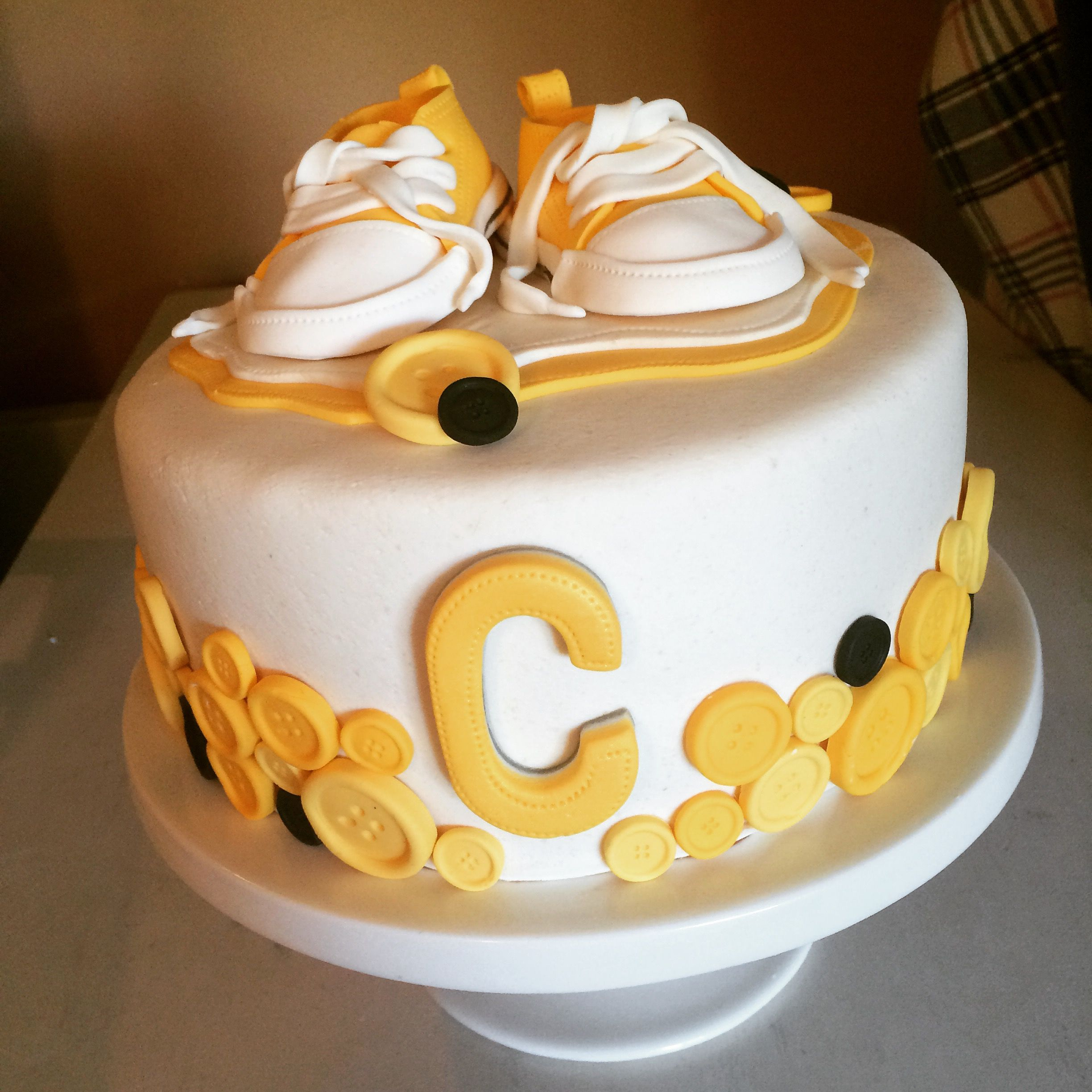 A christening cake with fondant buttons and gumpaste converse.