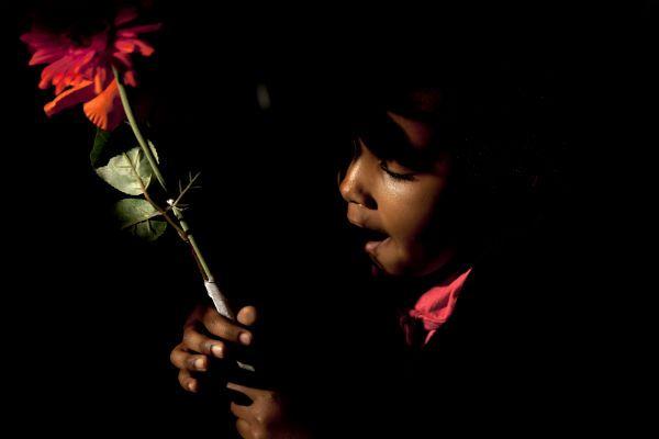 Una niña de una comunidad en Pretoria sostiene una flor mientras tararea canciones religiosas a favor de la salud del presidente surafricano Nelson Mandela. (AP)