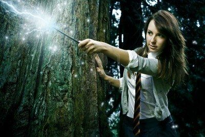 Photo of Teenage wizard girl with magic wand casting spells in a enchanted..