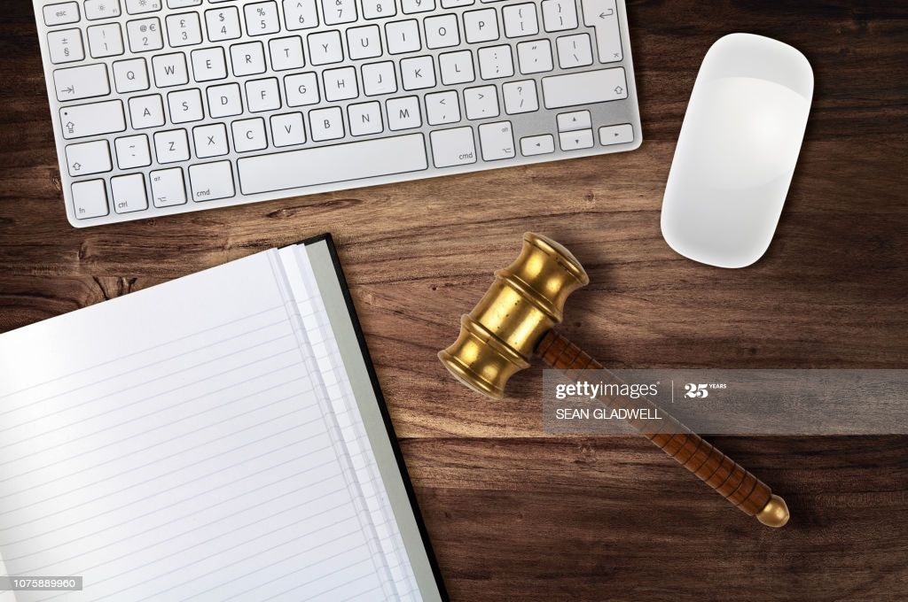 Gavel on desk beside computer and notepad