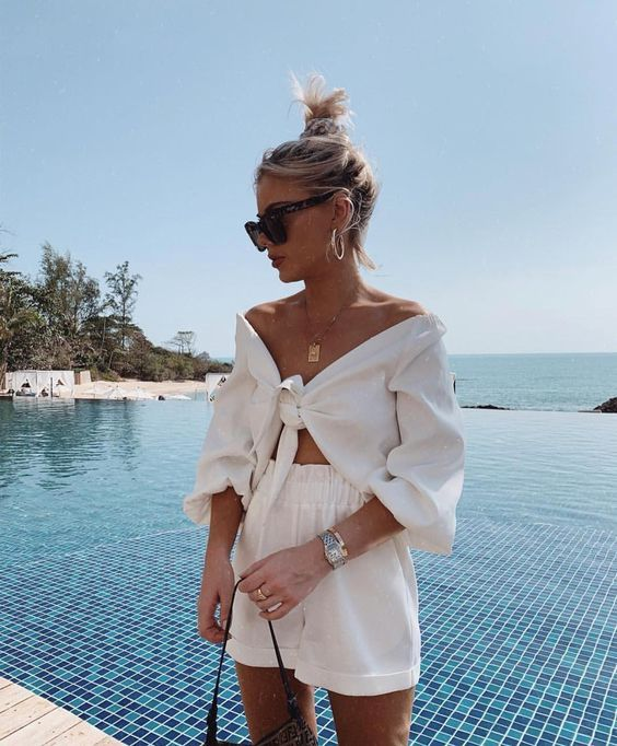 Summervibes | Summer outfit | Zomer outfit | Holiday vibes | White outfit | Witte top | Off shoulder top | High waisted shorts | Black sunglasses | Golden jewellery | Gouden ketting | Bun | Knot | Blond haar | Swimming pool | Vacay | Beauty | Inspiration | More on Fashionchick