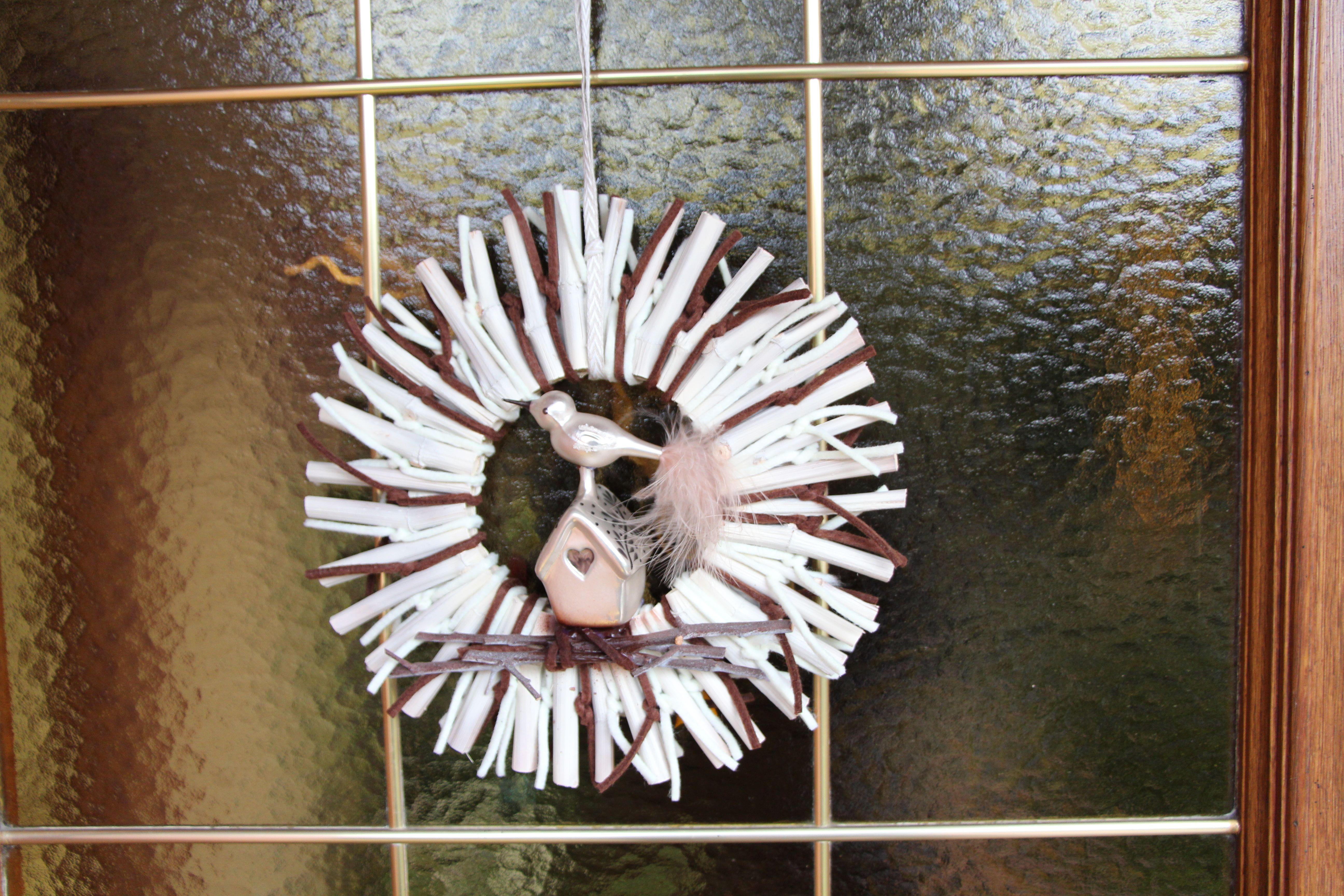 Eine Sonne aus weiß gefärbten Knöterich, naturfarbenen und braunen Filzbändern für eine Haustür aus Eichenholz. Die Mitte zieren ein Häuschen und Vogel aus Glas.