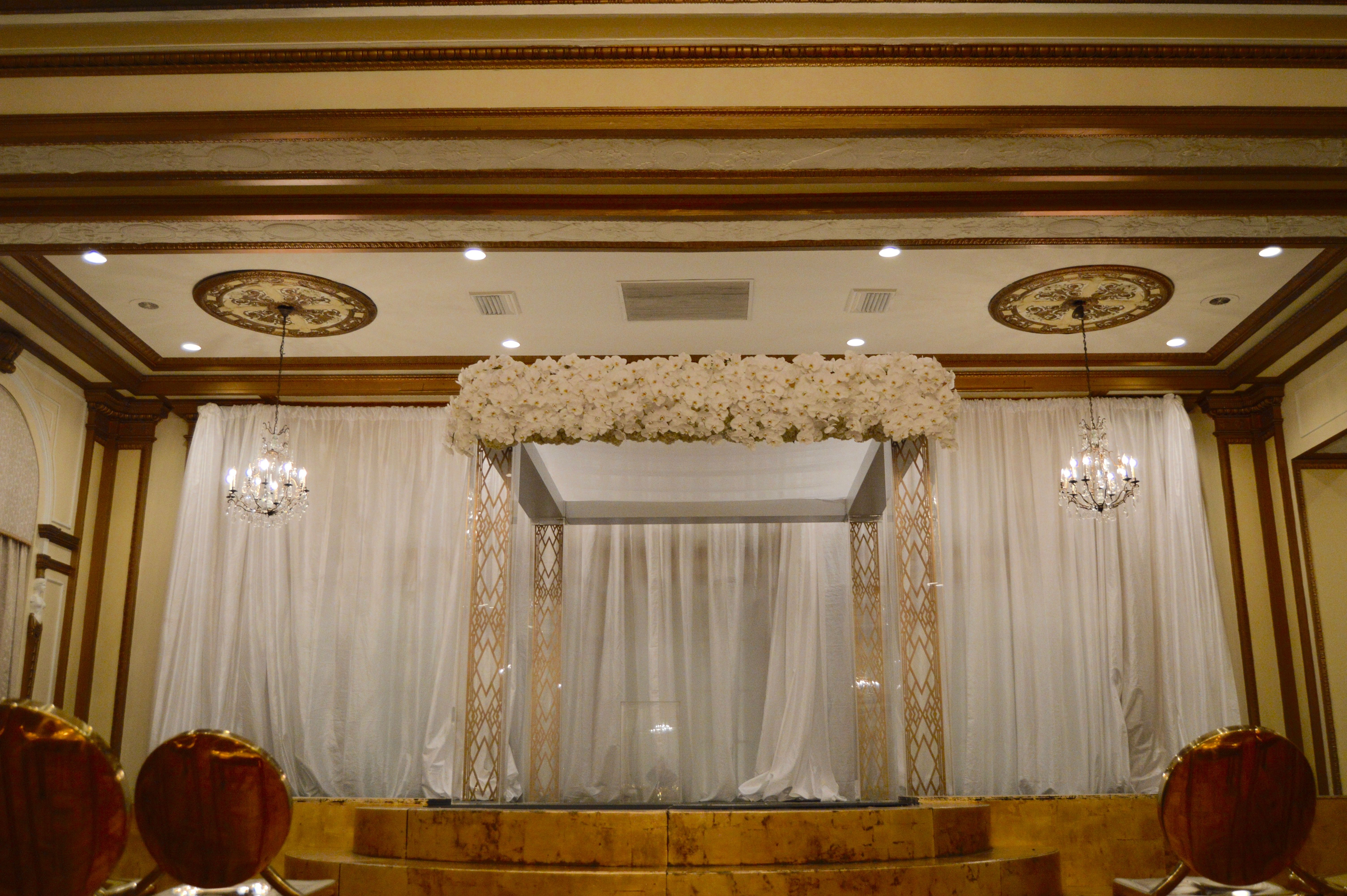 Custom Chuppah in the Venetian Room. Acrylic legs and solid floral top.