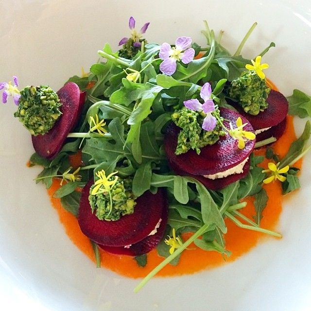Happy Spring!!!   What is this garden of a dish? It's beet ravioli with macadamia ricotta, red pepper sauce, arugula, and edible flowers, of course. I learned how to make this in my @matthewkenneycuisine class over a year ago. It was delicious. As you can see, my style is very rustic. I prefer it that way.   Who's excited for Spring?!  thewholesomes