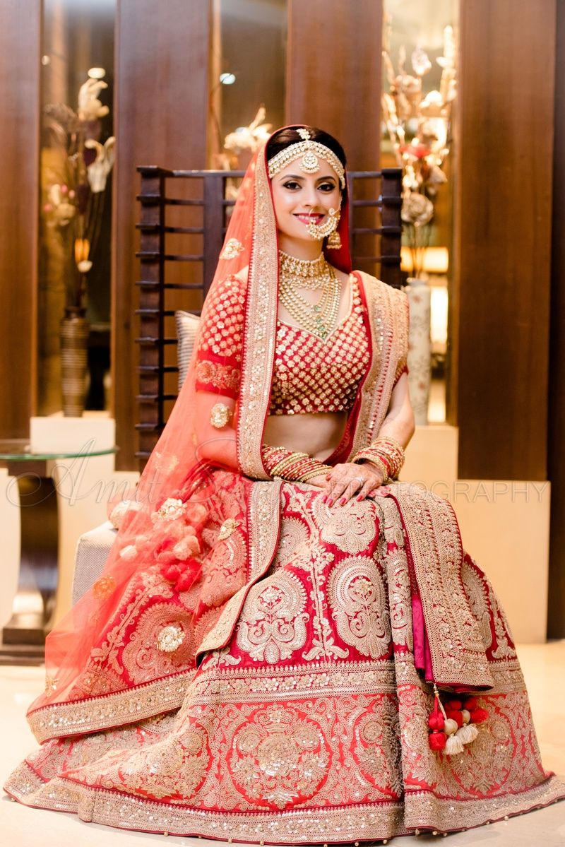 Bride In Red Bridal Lehenga And Gold Motifs