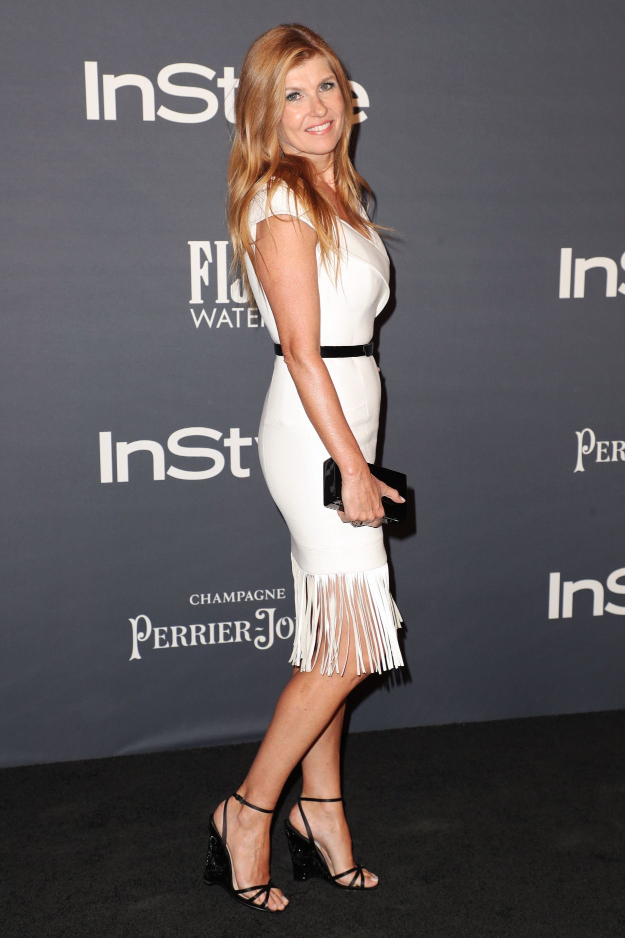 efec5791143f Connie Britton nice legs in a little white dress with bottom fringe and  ankle strap high heels