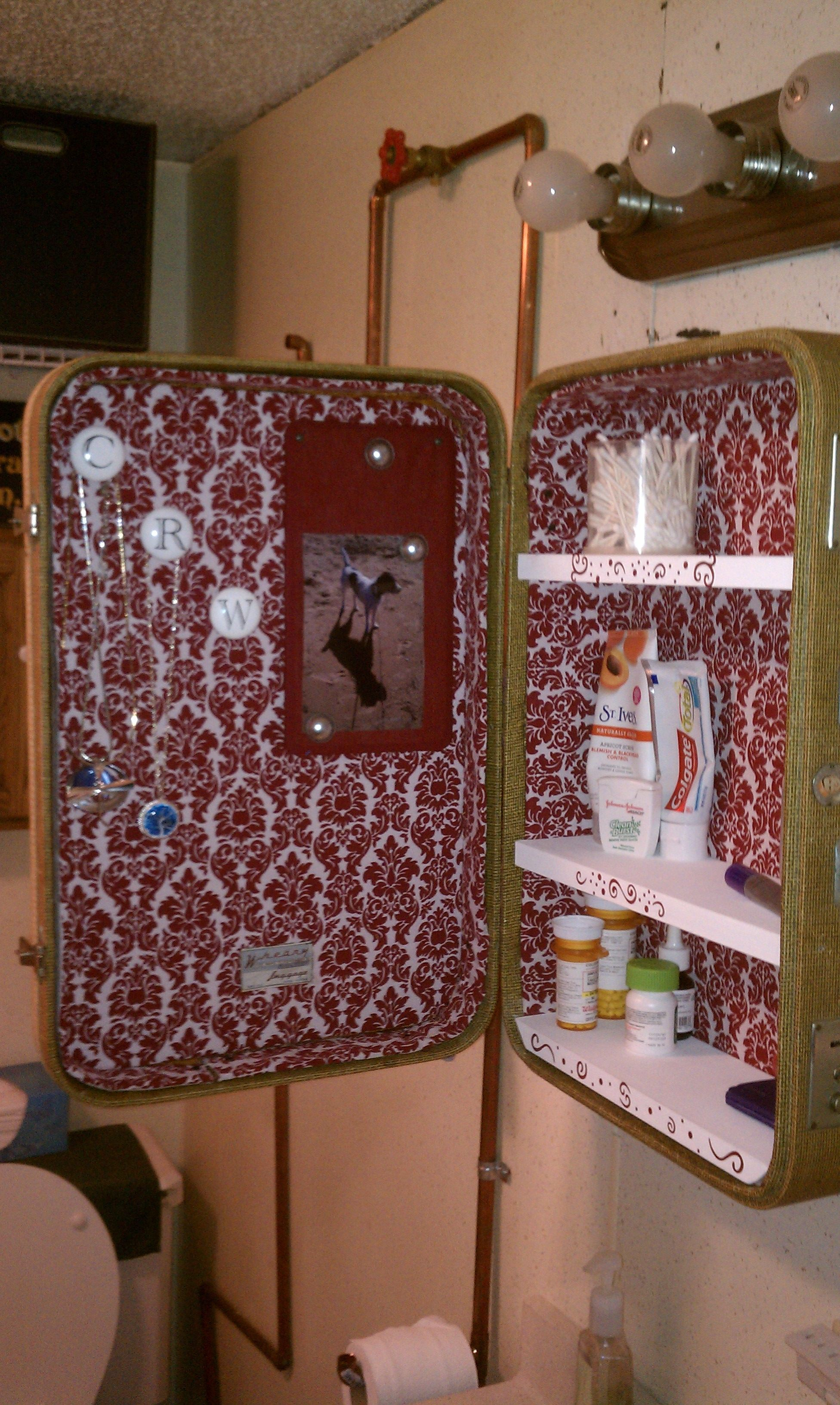 Inside of my upcycled vintage suitcase turned medicine cabinet! (w/door knobs to hang jewelery and a magnet board for pics, etc)