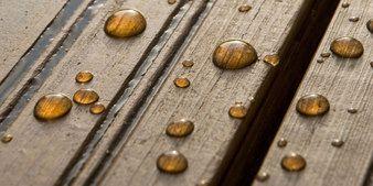 Puuöljytyllä pinnalla vesi pisaroi