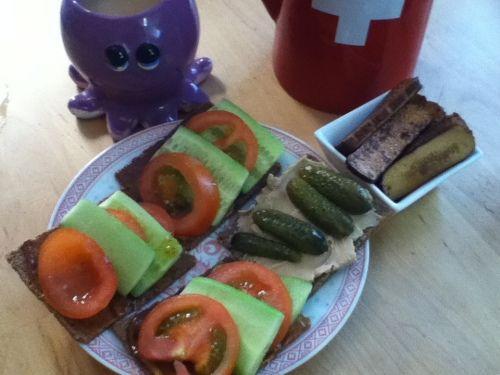 Roses Frühstück in Scheiben: Urdinkelbrot, angebratener Räuchertofu, Tartex-Aufstrich, Senf/Cenovis-Mischung, Gurke, Tomate und Essiggürkchen, dazu Zimt-Schwarztee mit Vanille-Hafermilch und Stevia.