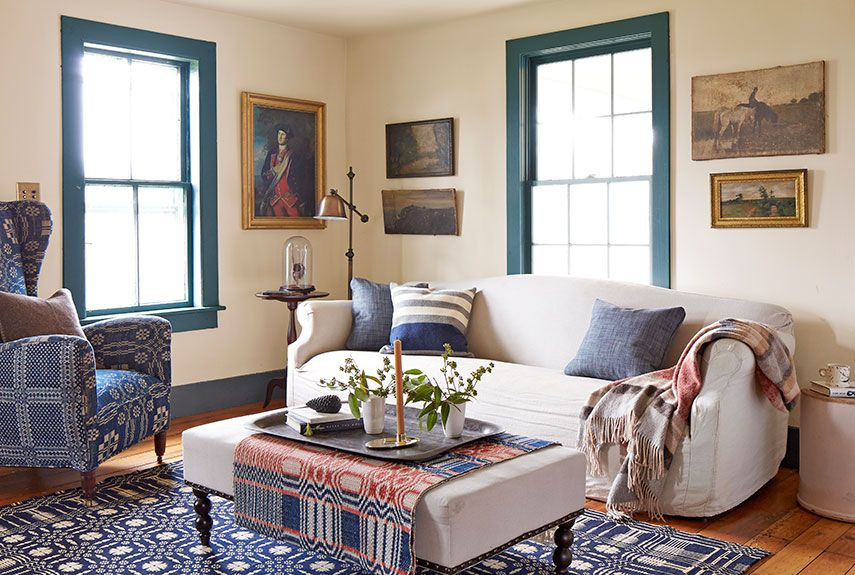 This Catskills home's remote location renders window treatments unnecessary. In the living room, mid-1800s homespun blankets cover the wing chair, ottoman, and hardwood floor. The slipcovered sofa is from ABC Carpet & Home. The windows are painted Everard Blue and the walls are Montgomery White, both by Benjamin Moore.   - CountryLiving.com