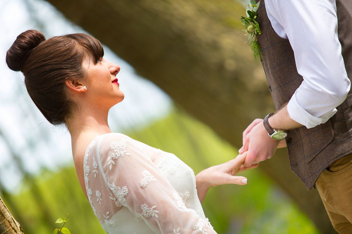 The groom places the wedding ring on his bride's finger during their ceremony in the bluebell woods at Jimmy's Farm, Suffolk. www.headoverheelsphotography.co.uk