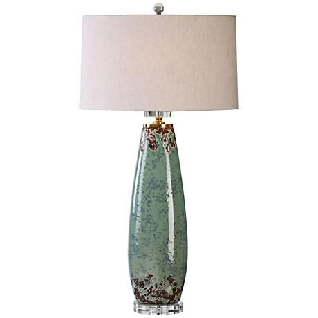 Rustic and refined in the same moment this transitional ceramic table lamp balances a crystal foot and a charming crackle finish in pale green with rust