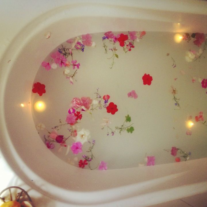 Lotus Flower Pods In A Tub With Floating Candles In A Milk