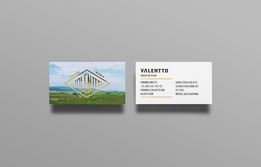 Logo and business card with gold foil and photographic landscape detail designed by Anagrama for olive oil brand Valentto