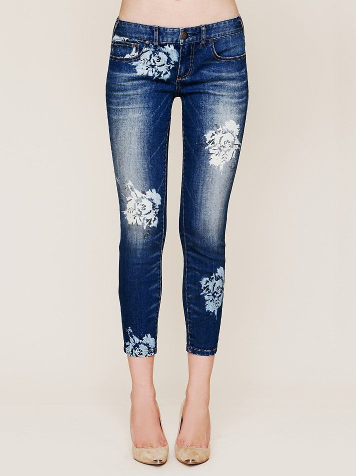 Paint flowers onto jeans using stencils