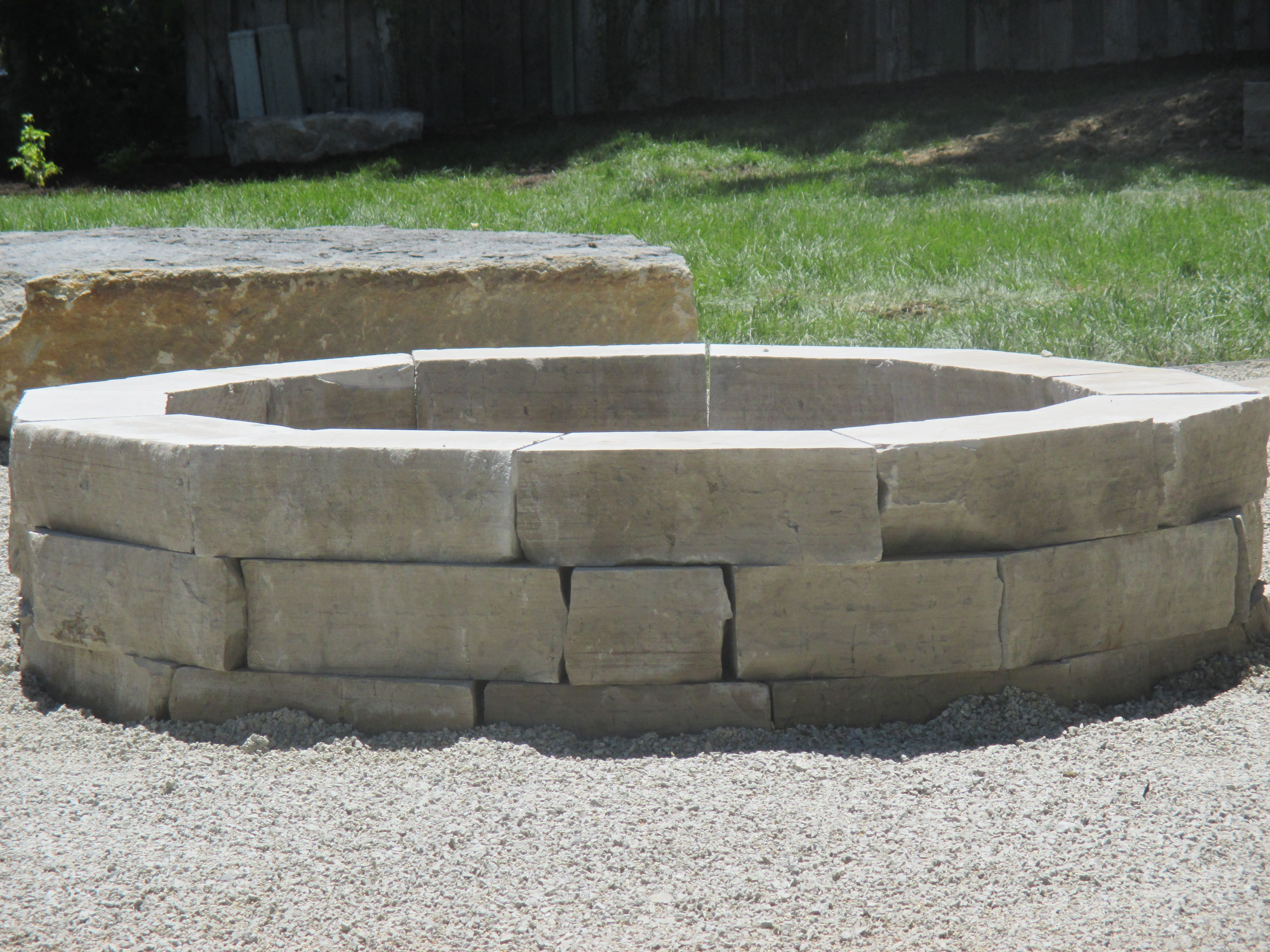 Limestone Fire Pit Set In Crushed Gravel Patio.