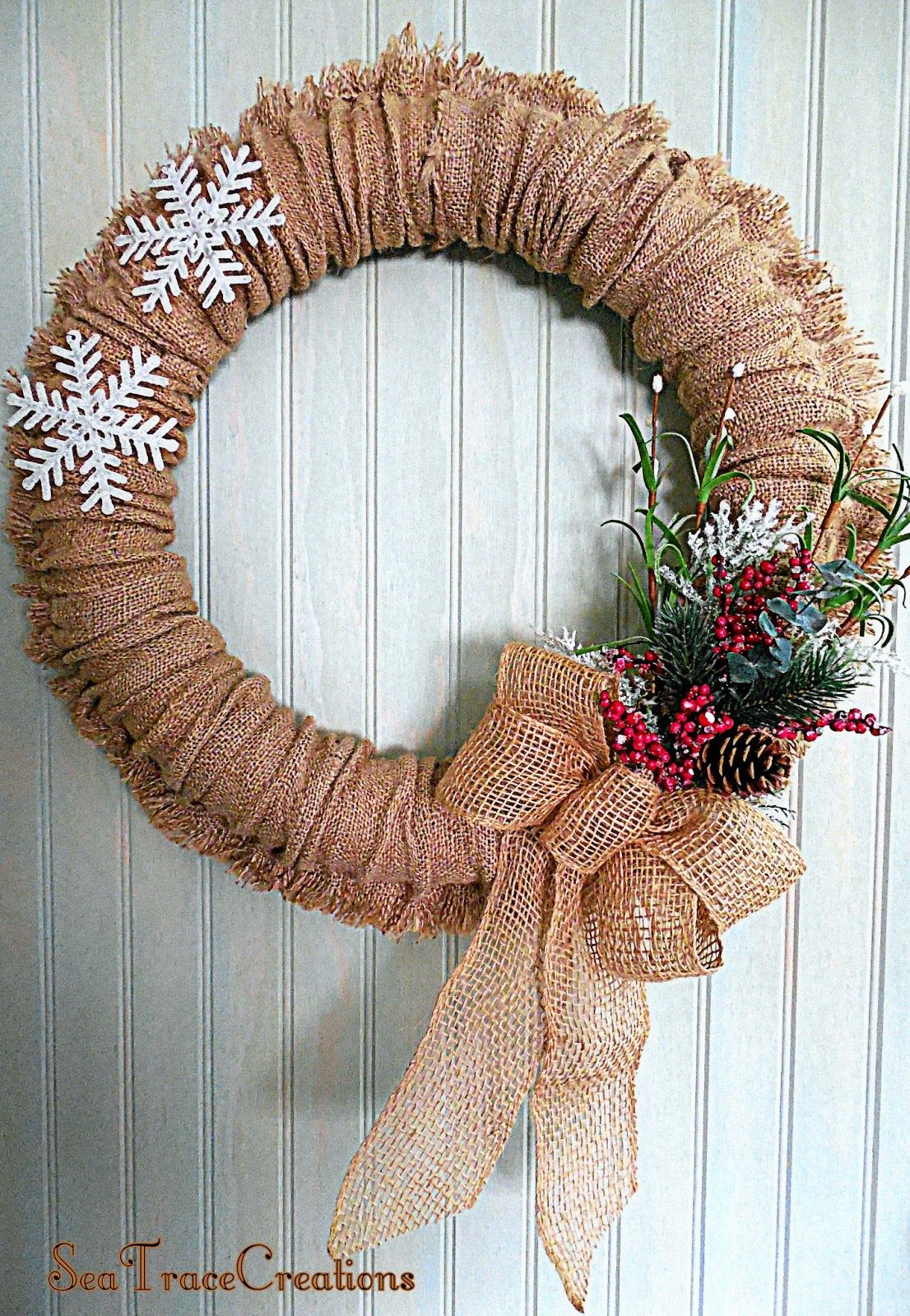 Burlap Pool Noodle Wreath made by Sea Trace Creations. It is designed to be used year round as the flower boutineer and snowflakes are temporarily pinned onto the wreath. Both can be opted out in the Spring for seasonal flowers and maybe some butterflies.