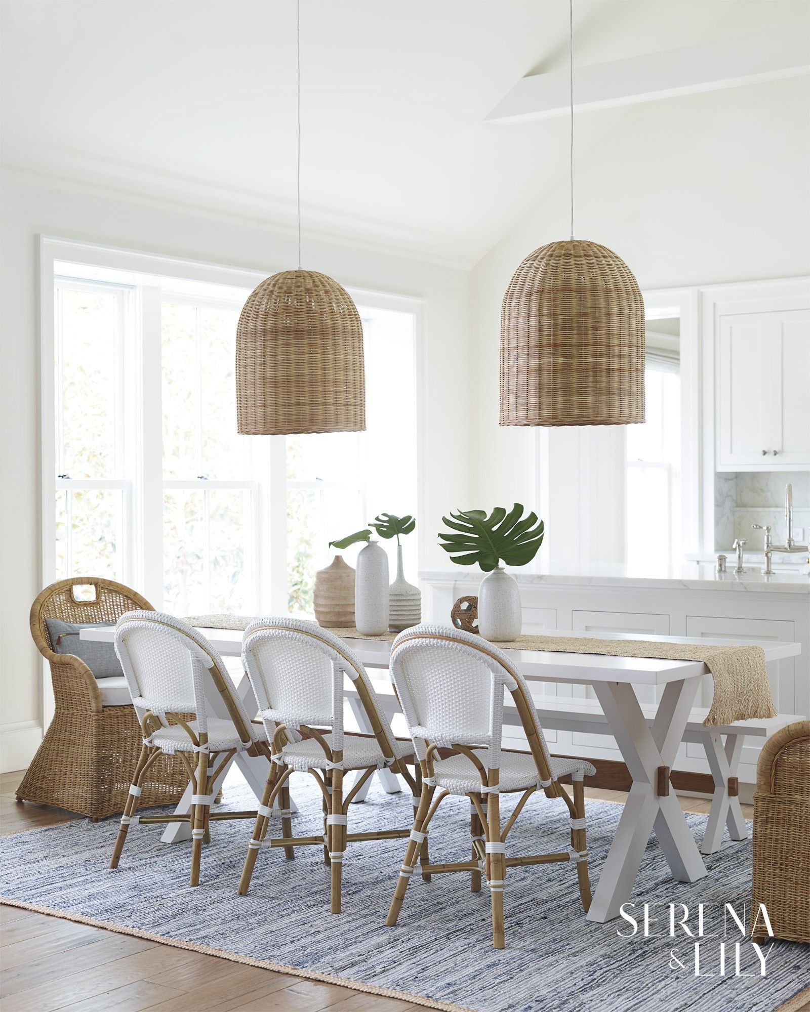 This White Dining Room Emanates Chic Beachy Vibes With Its French Bistro Chairs Rattan Light P Dining Room Design Dining Room Inspiration Coastal Living Rooms