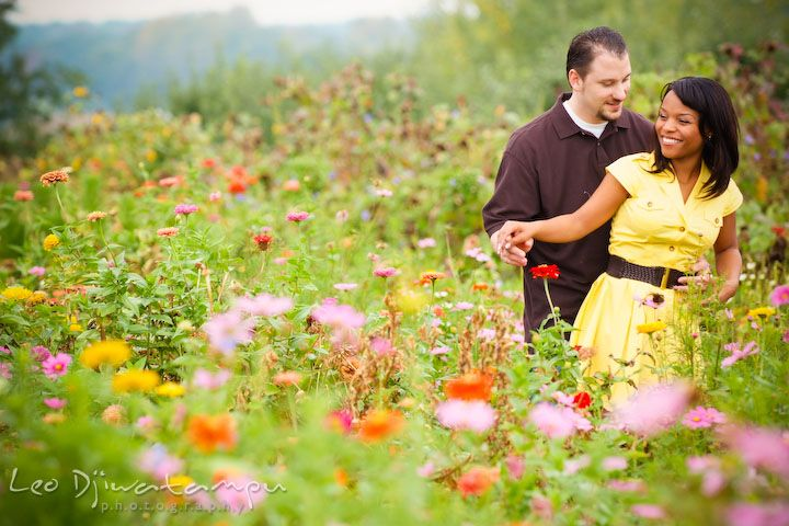 Engaged couple dancing in a flower field engagement pre wedding photo session fruit tree