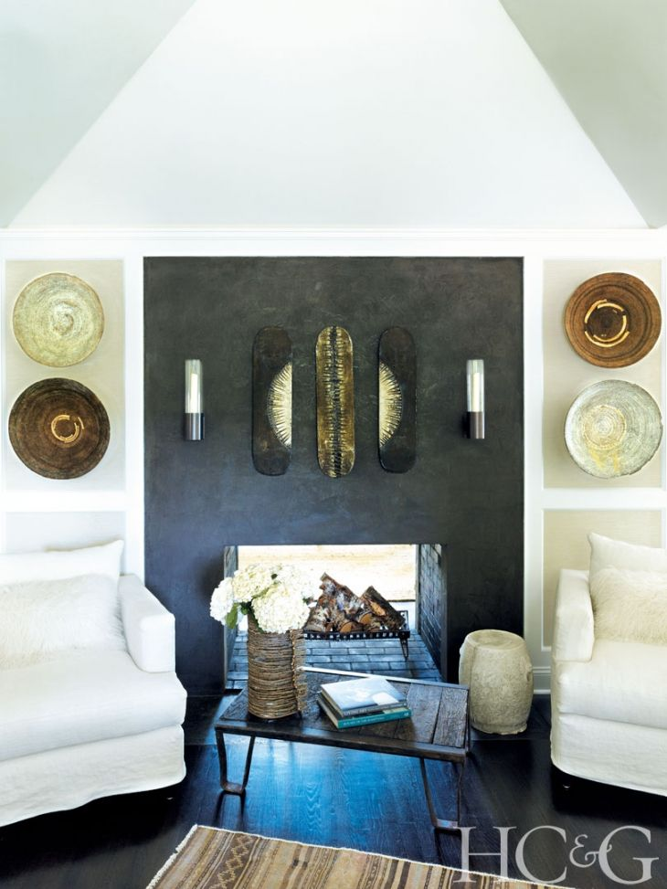 Installed above the kitchen fireplace, a pair of sconces by Greg Yale lends modern contrast to a trio of African skateboards.