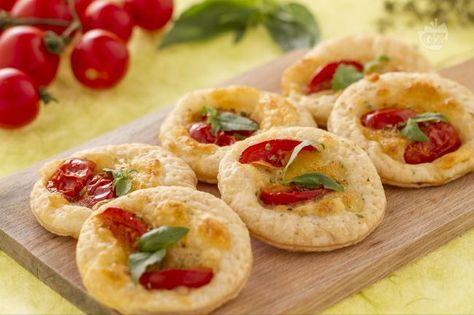 Le sfoglie capresi sono uno sfizioso finger food fatto con una base di pasta sfoglia, mozzarella e pomodorini, condite con origano e basilico.