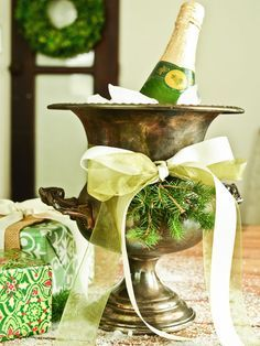 Dress up a urn with fresh greenery and a festive bow for a stylish wine cooler.
