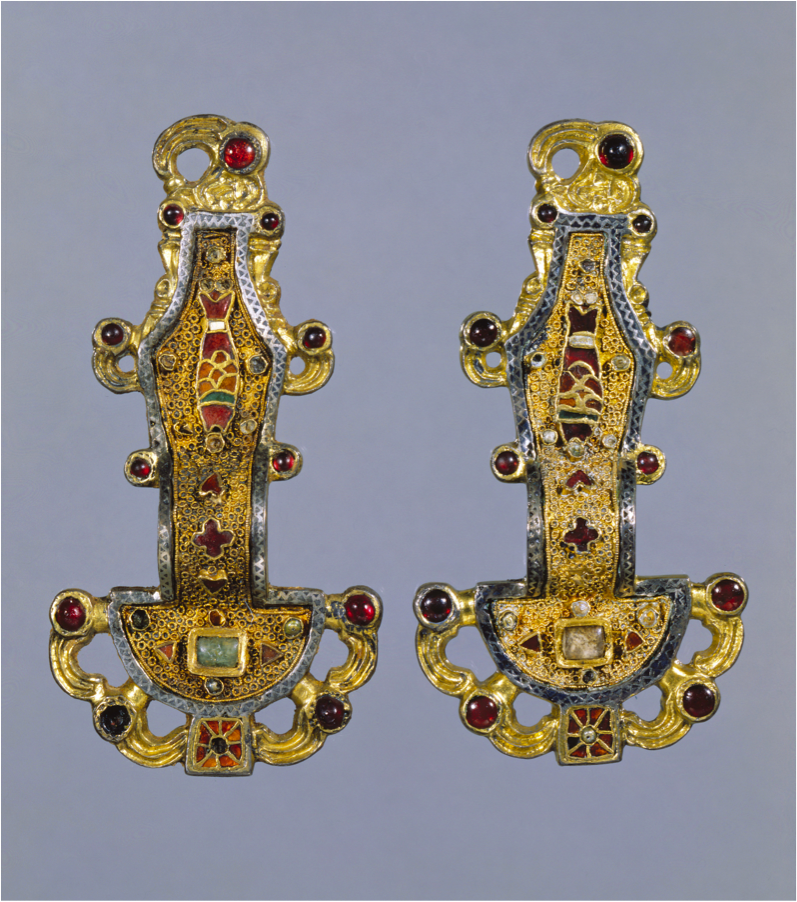 [Unknown, Merovingian looped fibulae, mid-sixth century, silver gilt with garnets and other stones, Early Medieval] Fibulae were one of the most characteristic garments that provided cultural information about barbarian arts for it displays a sense of how wealthy people dressed at the time. Artists favored flat and abstract representations of people and animals; they also use interlaced patterns of decorative gold and garnets to characterize popular motifs of zoomorphic elements. (Ross…