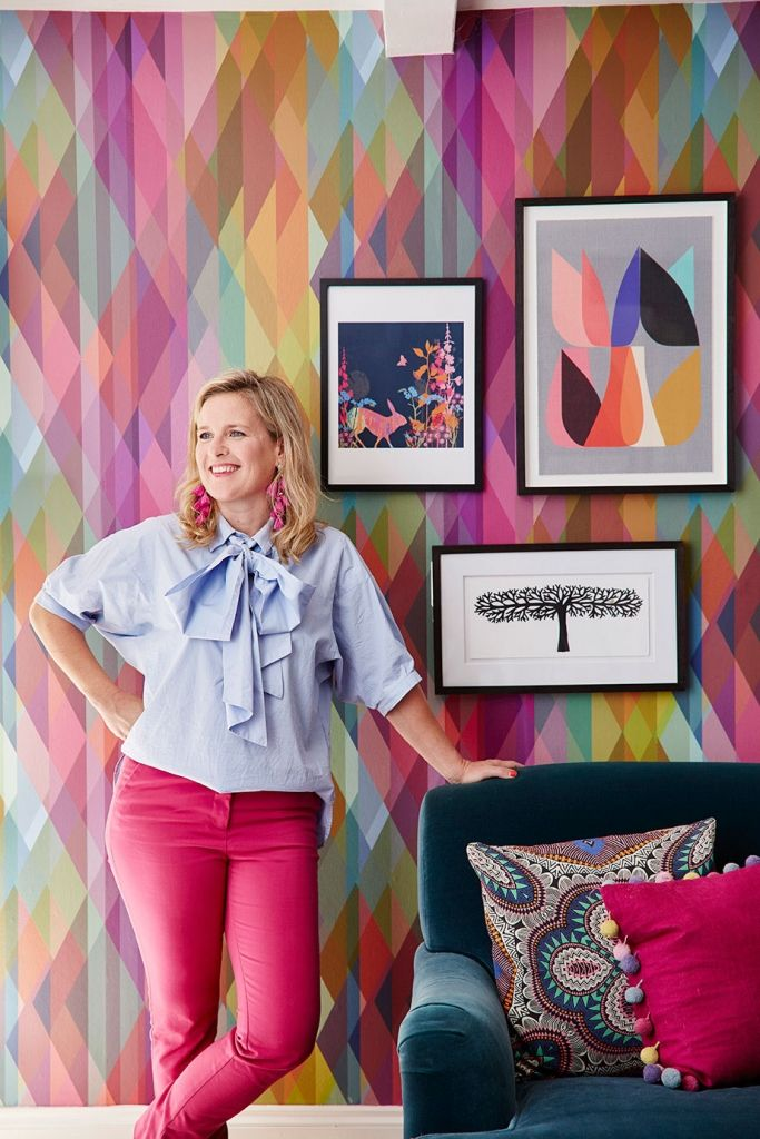 Interior designer sophie robinson love shanging artwork in her home decor to make a space feel quirky and colourful wearing pink trousers and pale blue
