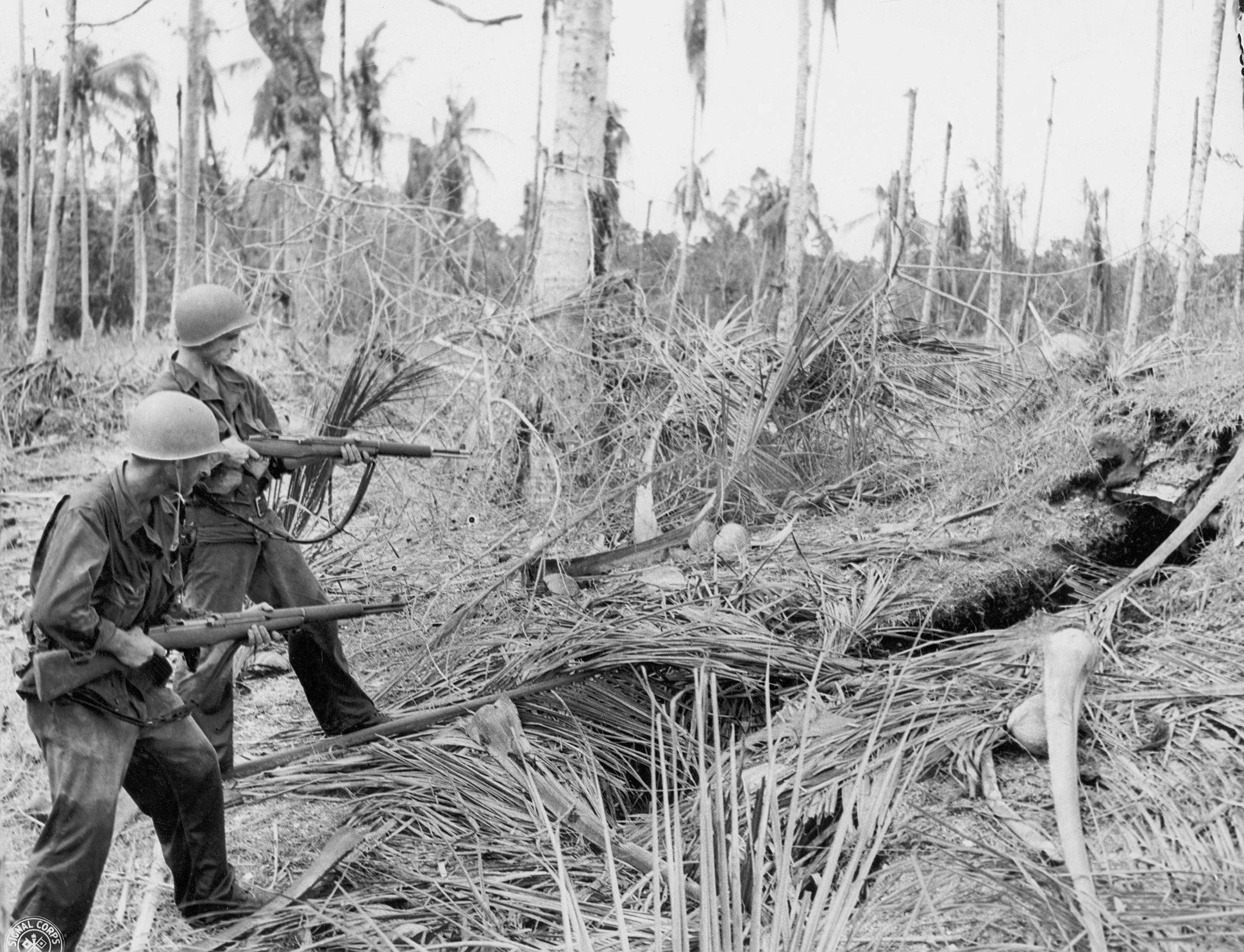 March 1943: Two GIs approach a Jap dugout in Boone, New Guinea and pepper its entrance with preparatory fire from their M1 Garand rifles. Dugouts were usually dealt with with flame throwers and grenades.