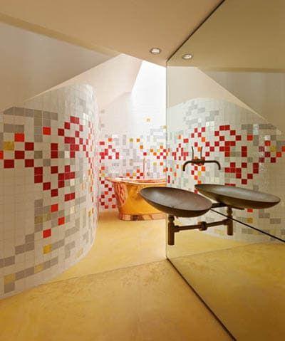 Baignoire dorée et mosaïque de couleur pour une salle de bain originale