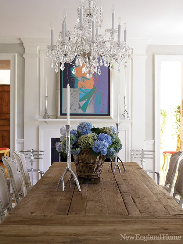 A crystal chandelier is an elegant counterpoint to the rough-hewn dining room table