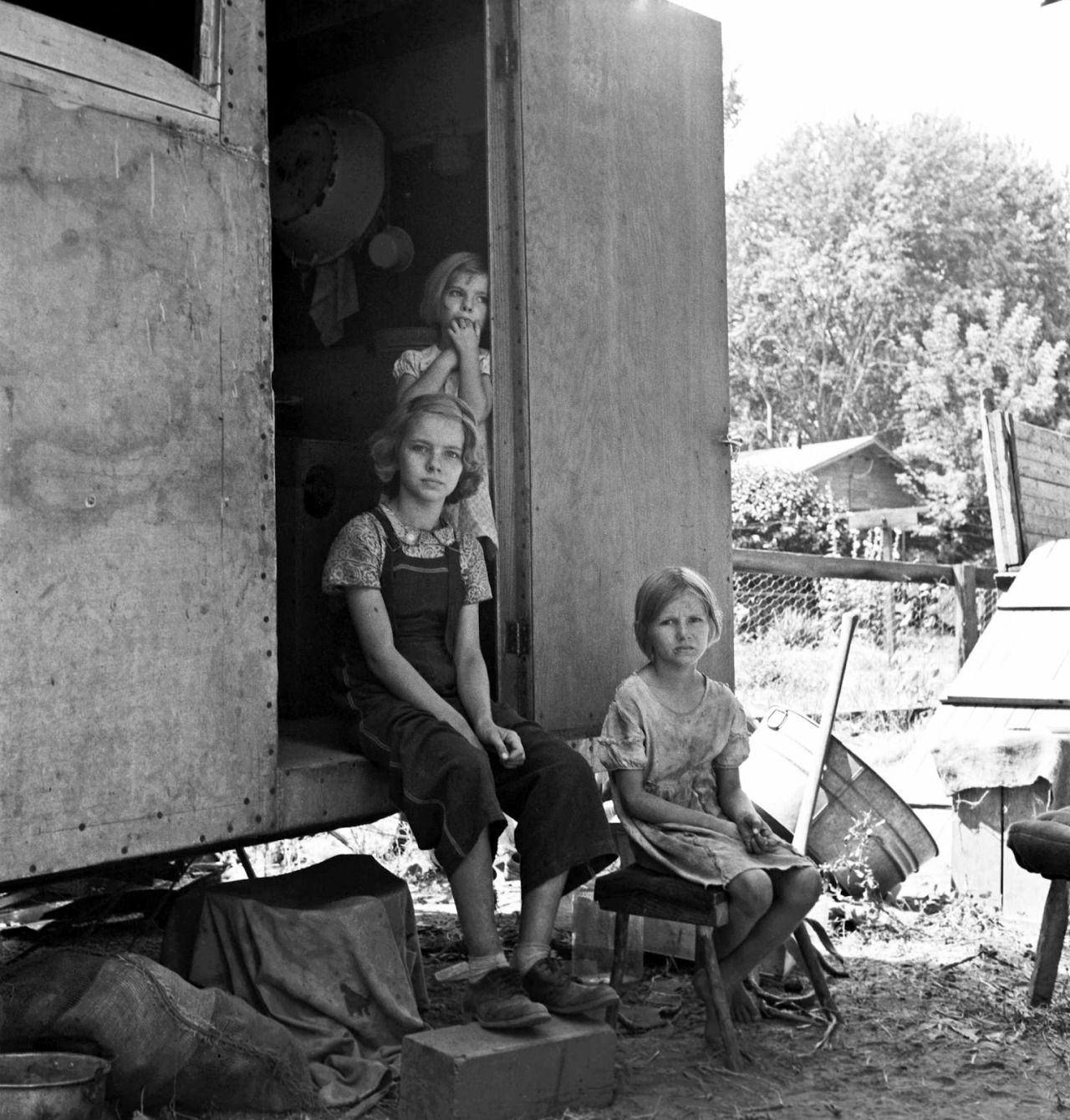 The oldest girl seated in the doorway of the house trailer cares for the family, Yakima Valley, Washington, 1939 by Dorothea Lange.