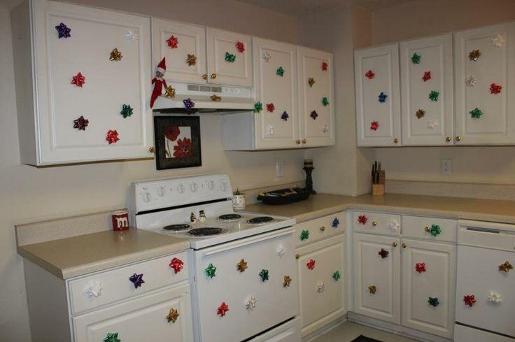Funny Elf On the Shelf Ideas | Elf on shelf decorates kitchen with sticky bows.