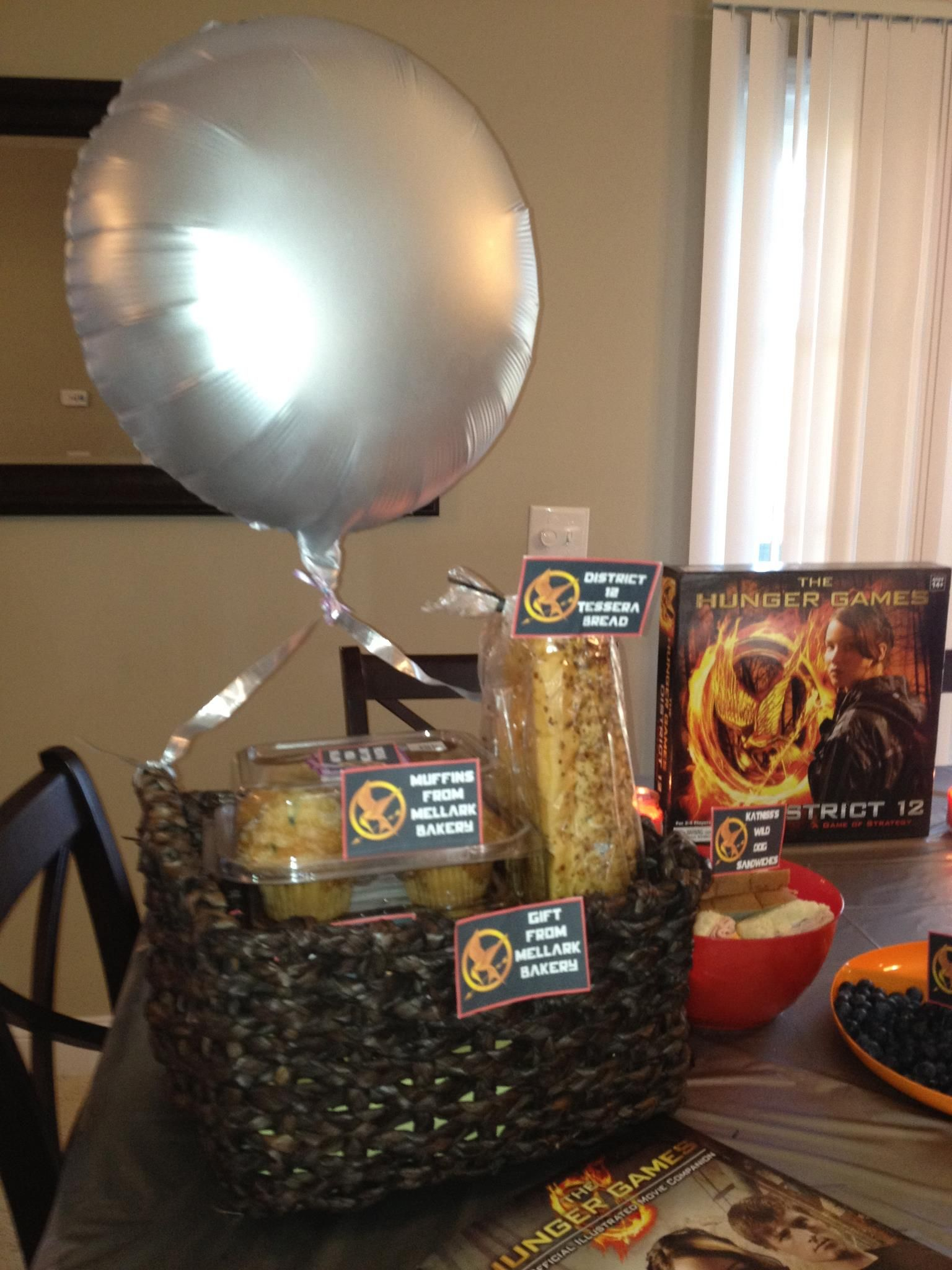 Hunger Games Party with print items from my company, Never Forgotten Designs! Basket from Michael's and balloon spray painted silver!    https://www.etsy.com/your/shops/NeverForgottenDesign/sections/11342200