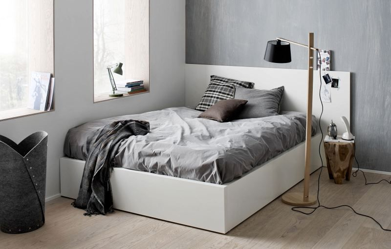 Reduced bed room styling with grey and some wood.