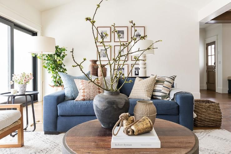 Denim Blue Sofa With A Round Black Salvaged End Table Accented With Decorative Pieces Atop Blue Sofas Living Room Blue Couch Living Room Blue Living Room Decor