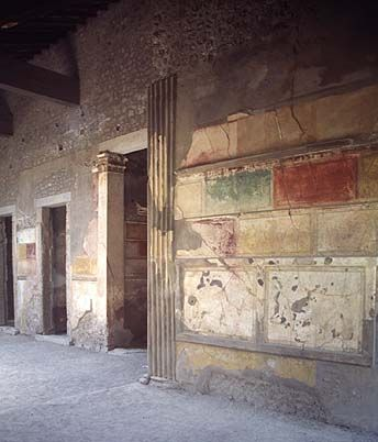 "Roman Fresco First Style in House of the Tragic Poet (Sallust). ""The First style, also referred to as structural, incrustation or masonry style, was most popular from 200 BC until 80 BC. It is characterized by the simulation of marble (marble veneering), with other simulated elements (e.g. suspended alabaster discs in vertical lines, 'wooden' beams in yellow and 'pillars' and 'cornices' in white), and the use of vivid colour, both being a sign of wealth.""Wikipedia"
