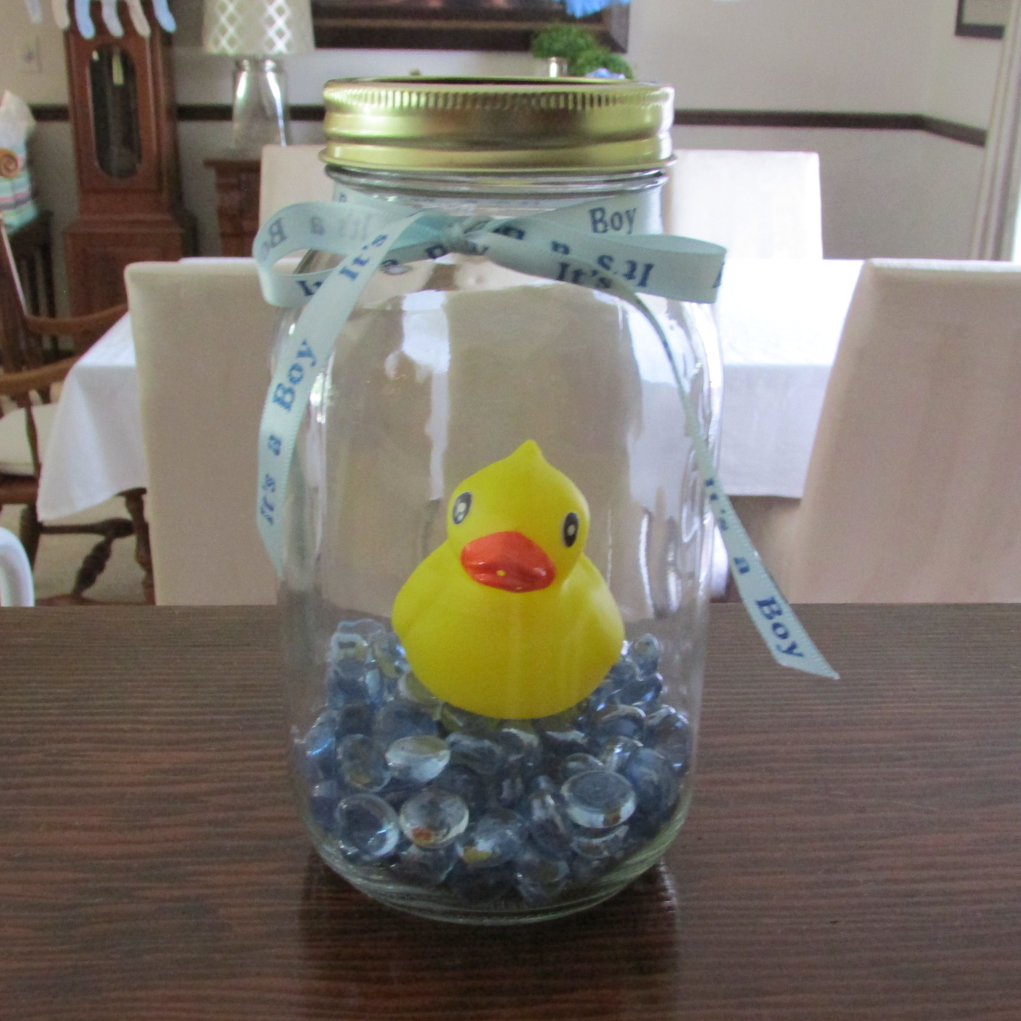 rubber ducky themed baby shower mason jars with cotton balls mason jar with blue glass rocks a normal size rubber duck and a ribbon of