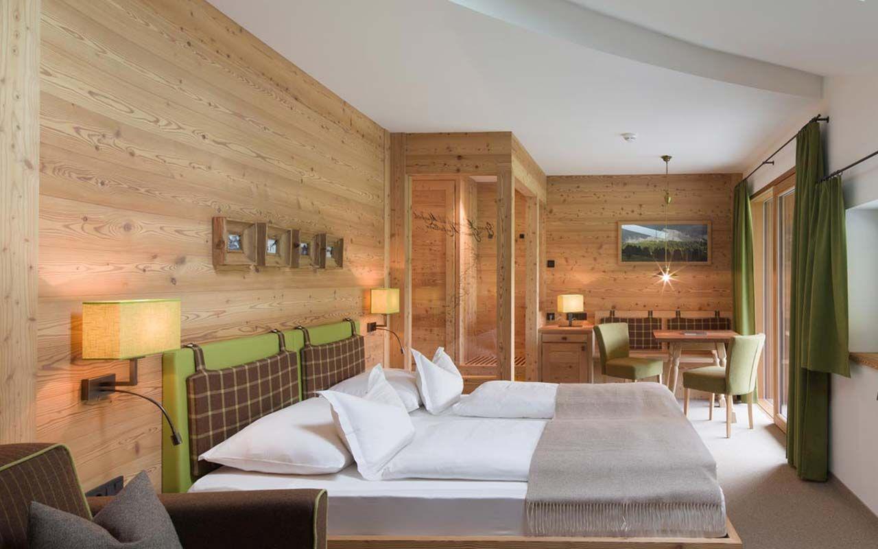 Camera da letto con pareti in legno, tende verdi e letto matrimoniale con testiera verde