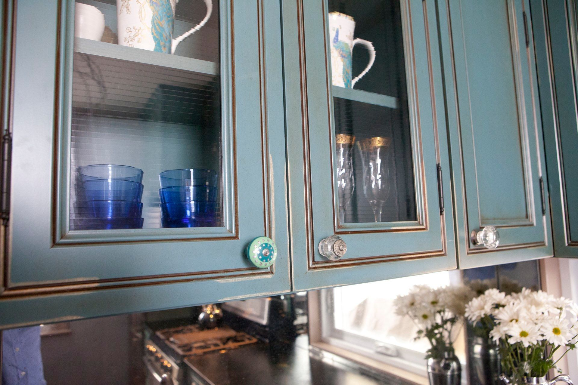 A mirrored backsplash and these glass cabinets give this small but ...